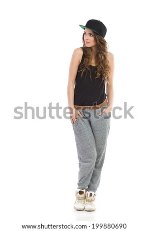 Young woman posing in gray track-suit, black top and full cap posing and looking away. Full length studio shot isolated on white. - stock photo