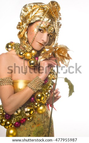 Young woman posing in holiday artistic image with New Year decoration and with golden flower.