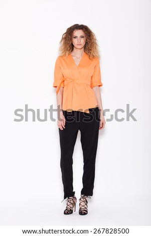 young woman posing in orange kimono and black pants, on white background - stock photo
