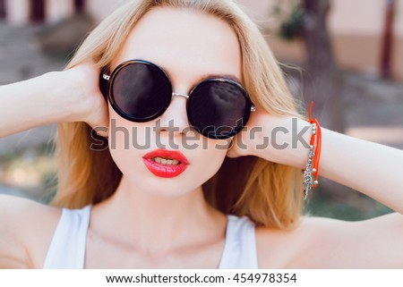 young woman posing in the street in sunglasses, outdoor portrait, hipster style, fashion model, close up art, sunglasses, red lips, emotional, street photo, selfie - stock photo