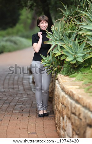 young woman posing near a bush of aloe vera