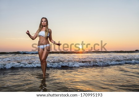 Young woman posing on beach at sea. Sunset time outdoor portrait