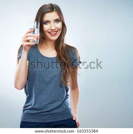 Young woman posing on isolated studio background, hold water glass. Beautiful girl portrait. Female model poses. - stock photo