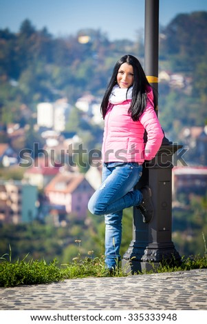 Young woman posing outdoor in autumn. Fashion portrait of pretty girl in cold weather wearing a pink jacket and jeans. - stock photo
