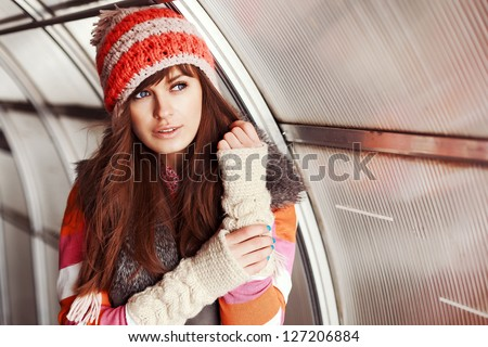 Young woman posing outdoor in winter. Fashion portrait of pretty girl in cold spring weather. - stock photo