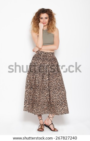 young woman posing relaxed on animal print skirt and green shirt on white background - stock photo