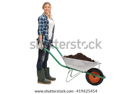 Young woman posing with a wheelbarrow full of dirt isolated on white background - stock photo