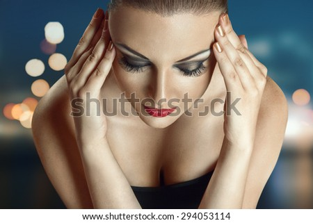 Young woman posing with night city lights in background - stock photo
