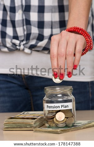 Young woman pouring coins into a jar. She is saving money for retirement. - stock photo