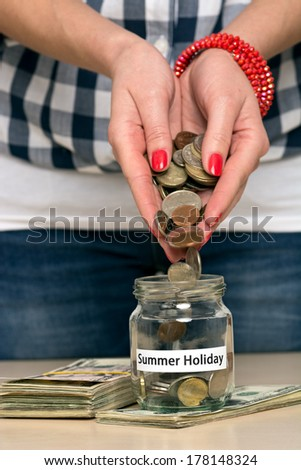 Young woman pouring coins into a jar. She is saving money for summer holiday. - stock photo