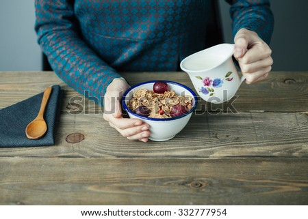 young woman pouring milk into cereal for breakfast on wooden table - stock photo