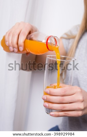 young woman pouring orange juice from the bottle to the glass - stock photo
