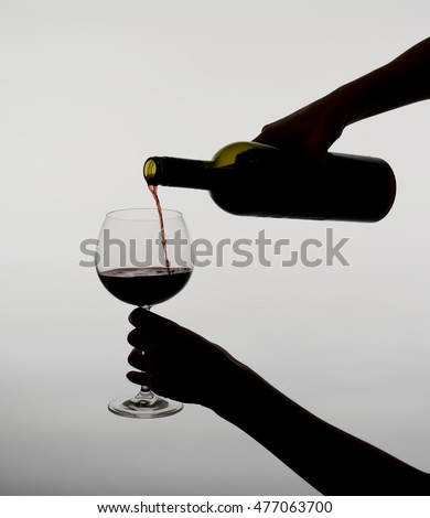 young woman pouring red wine , grey background