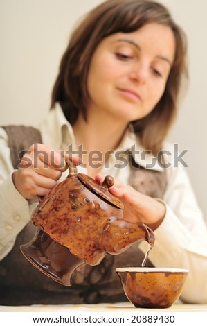 Young woman pouring tea with tea pot (chinese style) - focus on tea pot