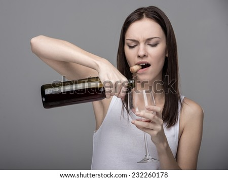 Young woman pours wine into a glass. Concept of bad habits. - stock photo