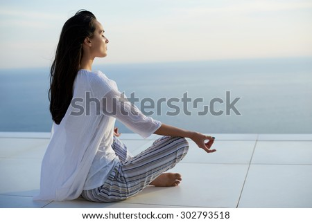 young woman practice yoga meditaion on sunset with ocean view in background - stock photo