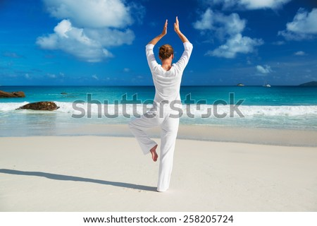Young woman practices morning exercises on the beach - stock photo