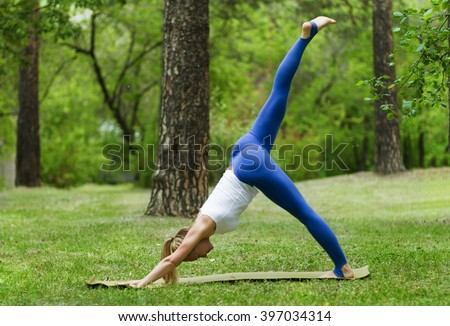 young woman practices yoga and gymnastics in the park, the mountain pose