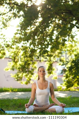 Young woman practices yoga in nature. Lotus Pose, eyes closed - stock photo