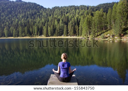 young woman practices yoga near mountain lake - stock photo