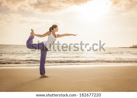 Young woman practicing dancer yoga pose on the beach during sunset - stock photo