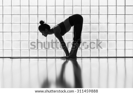 Young woman practicing in a yoga studio.