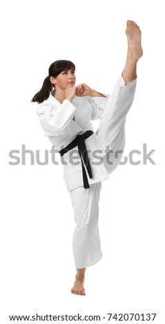 Young woman practicing karate on white background