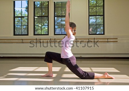 Young woman practicing Virabhadrasana Warrior 1 pose on floor.