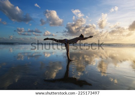 Young woman practicing warrior pose from yoga on the beach at sunset