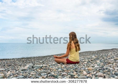 Young woman practicing yoga at seashore in summer