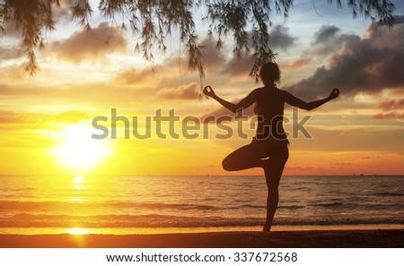 Young woman practicing yoga at sunset on the Ocean coast. - stock photo