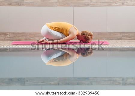 Young woman practicing yoga at swimming pool, Balasana / Child pose - stock photo