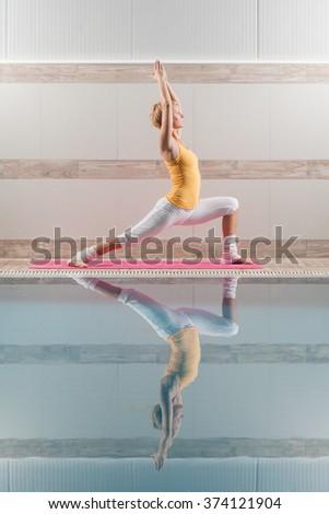 Young woman practicing yoga at swimming pool, Virabhadrasana / Warrior pose - stock photo