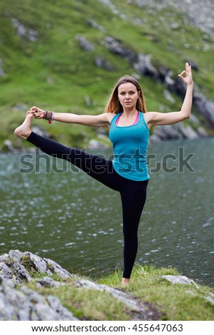 Young woman practicing yoga by a lake in the mountains