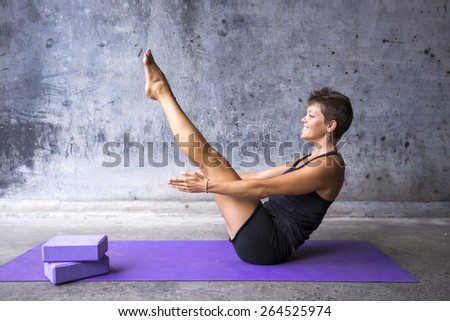Young woman practicing yoga in a urban background - stock photo