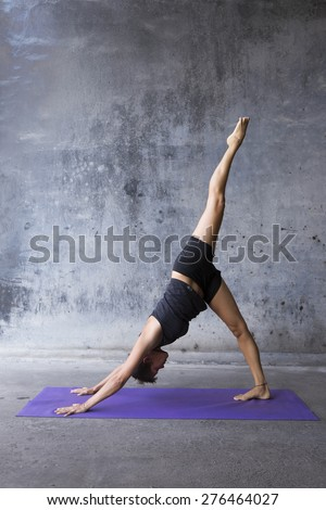 Young woman practicing yoga in a urban background