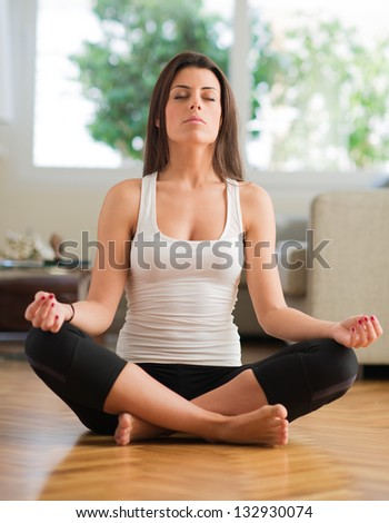 Young Woman Practicing Yoga In The Lotus Position, Indoors - stock photo