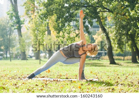 Young woman practicing yoga in the park,Yoga-Virabhadrasana  /Rotated warrior pose - stock photo