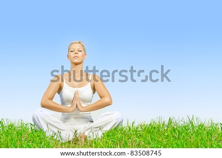 Young woman practicing yoga meditating outdoors with copyspace.