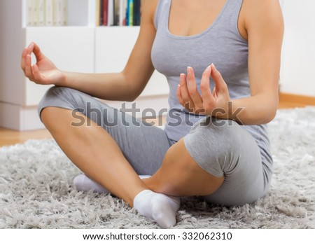 Young woman practicing yoga meditation at home. Fit caucasian female in sportswear exercising.Healthy lifestyle.