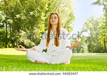 Young woman practicing yoga meditation in the park.