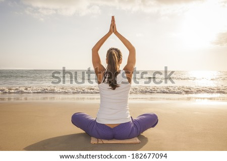 young woman practicing yoga meditation on the beach at sunset