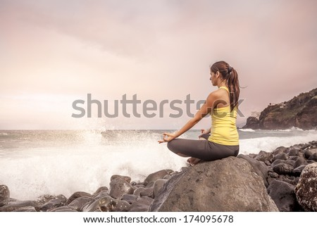 young woman practicing yoga meditation on the beach at sunset, lotus position