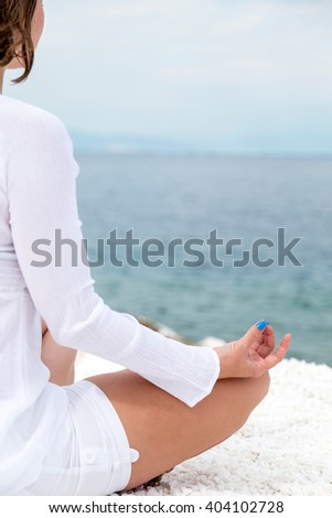 Young woman practicing yoga near marble beach on Thassos island, Greece on a cloudy summer day - stock photo