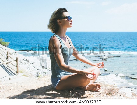 Young woman practicing yoga on a cliff, she meditating in lotus position.
