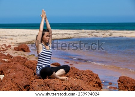 Young woman practicing yoga on beach rocks