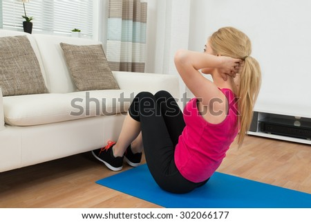 Young Woman Practicing Yoga On Exercise Mat In Living Room