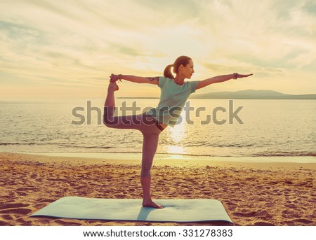 Young woman practicing yoga on mat on sand beach near the sea on sunset, woman in stretching balance pose