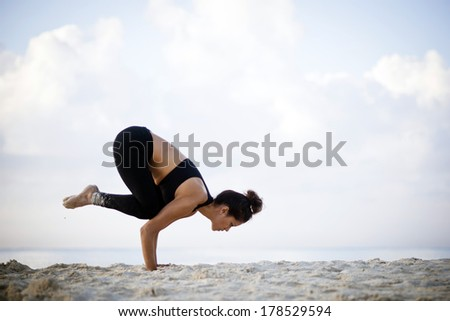 Young woman practicing yoga on the beach at sunrise - stock photo