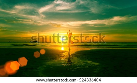 Young woman practicing yoga on the beach at weird sunset.